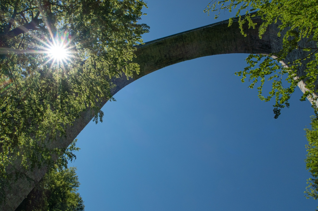 Arched bridge/viadukt taken from below, with a dominant blue sky, framed by trees, with a sunburst peeking through the trees