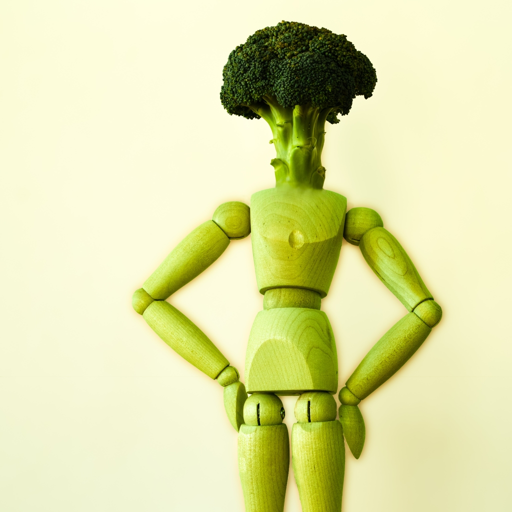 Wooden manikin standing in front of a yellow background. The manikin is green and its head is replaced by a broccoli.