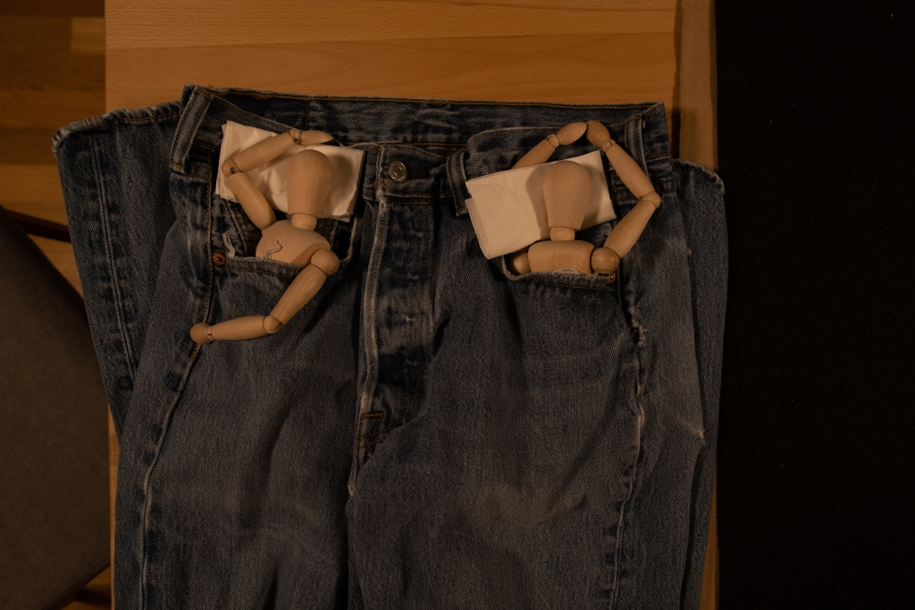 Pair of manikins, seemingly sleeping, tucked each in the pockets of a pair of jeans, using folded tissues as pillows.