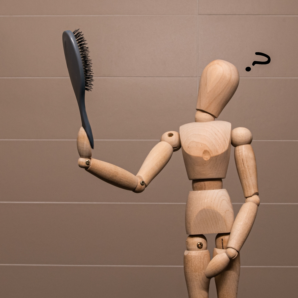 Wooden manikin looking at a hairbrush, looking puzzled.