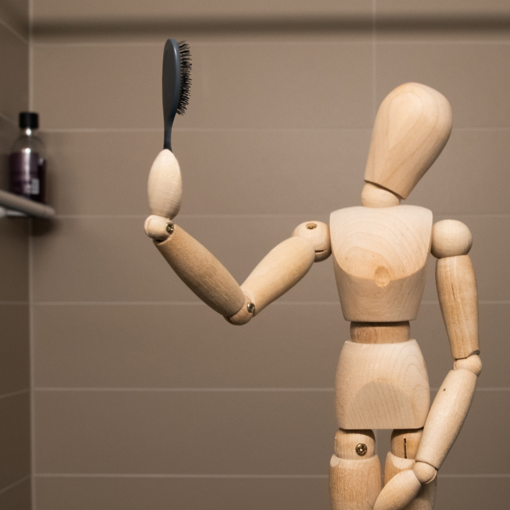 Bad composite of a wooden manikin holding a hairbrush in a way that's not remotely realistic.