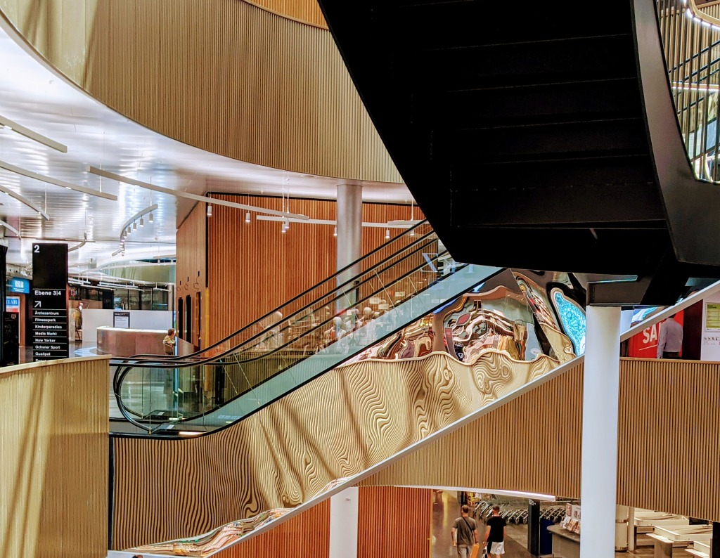 Escalators in a mall, where the reflection in the side panel is very distorted and yields interesting curves.