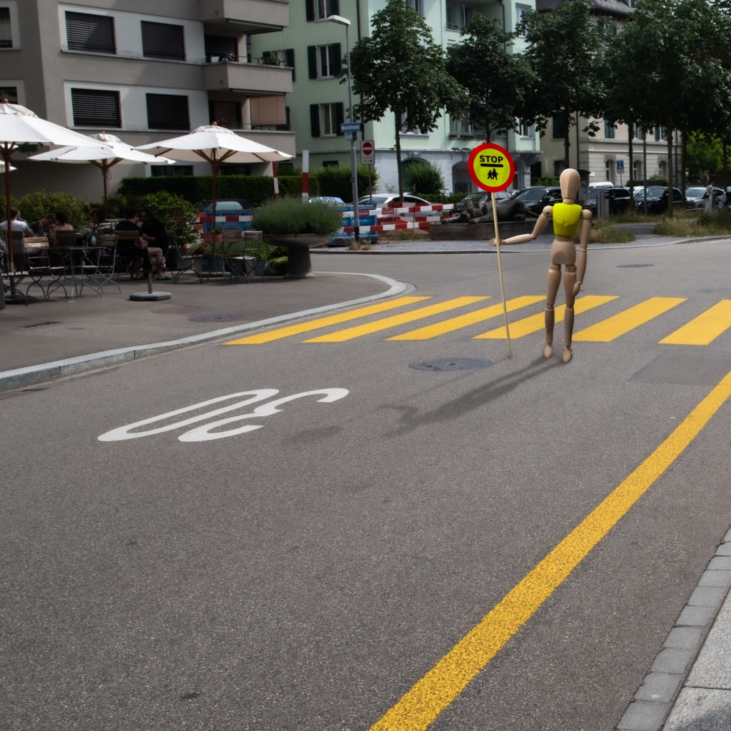 """Wooden manikin holding a large """"STOP / Children crossing"""" sign in front of a zebra crossing."""