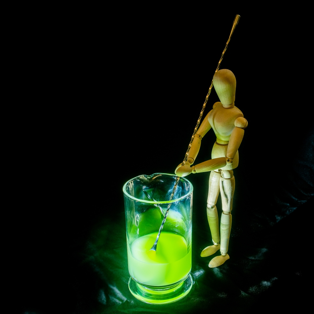 Wooden manikin stirring a bright green liquid with a giant spoon.