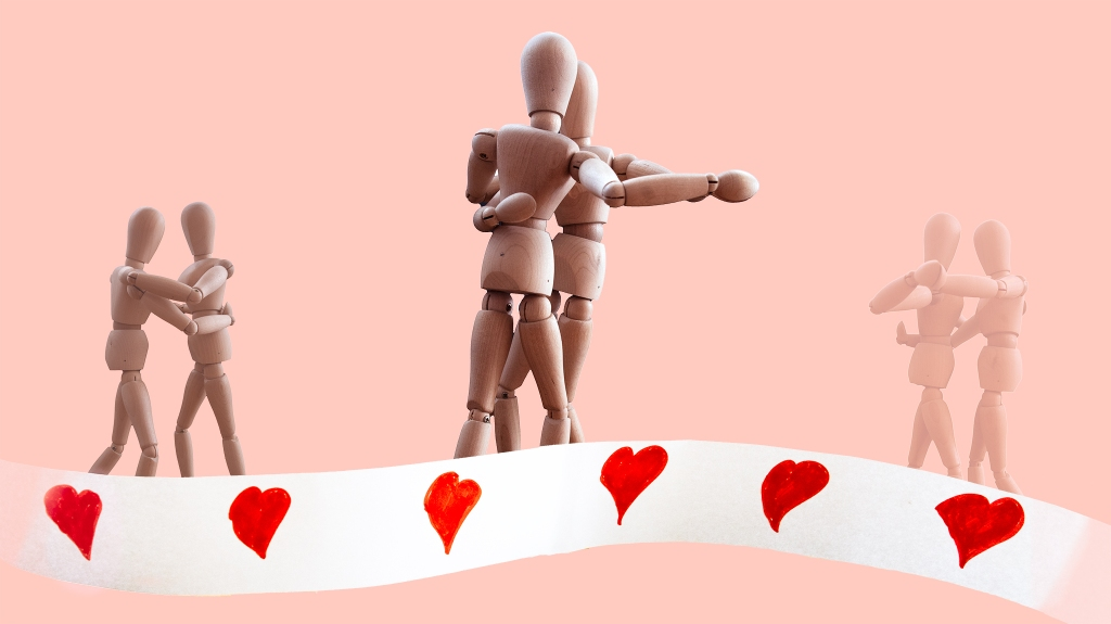 A couple of wooden manikins dancing. They are shown three times in the image (past, present, future; past and future are smaller and fainter); a banner of hearts at the bottom of the image symbolizes the passing of time.